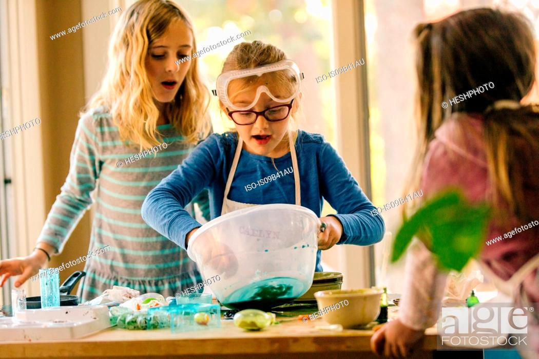 Stock Photo: Girls doing science experiment, mixing green liquid in bowl.