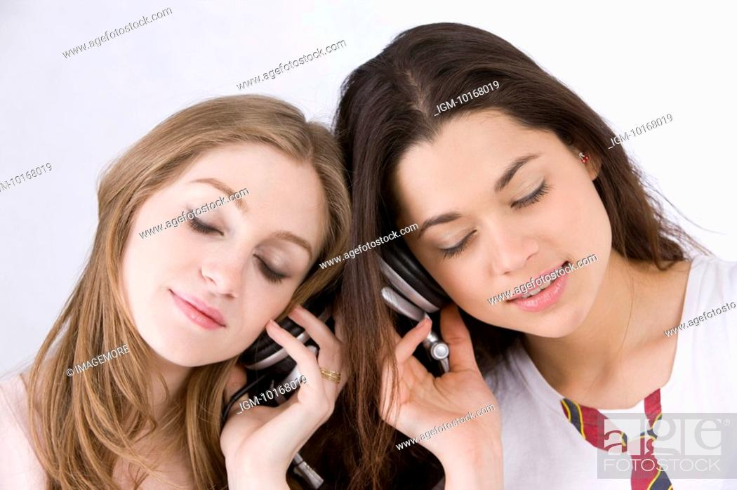 Stock Photo: Two young women sharing headphones.