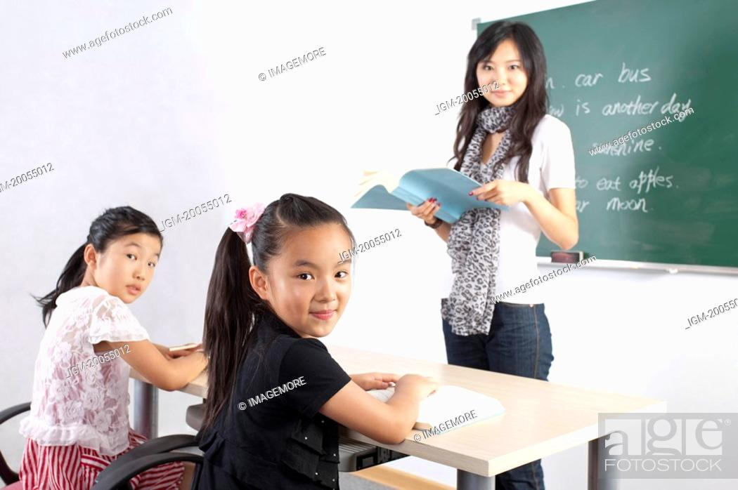 Stock Photo: Child, Children studying in the classroom and looking at the camera with teacher.