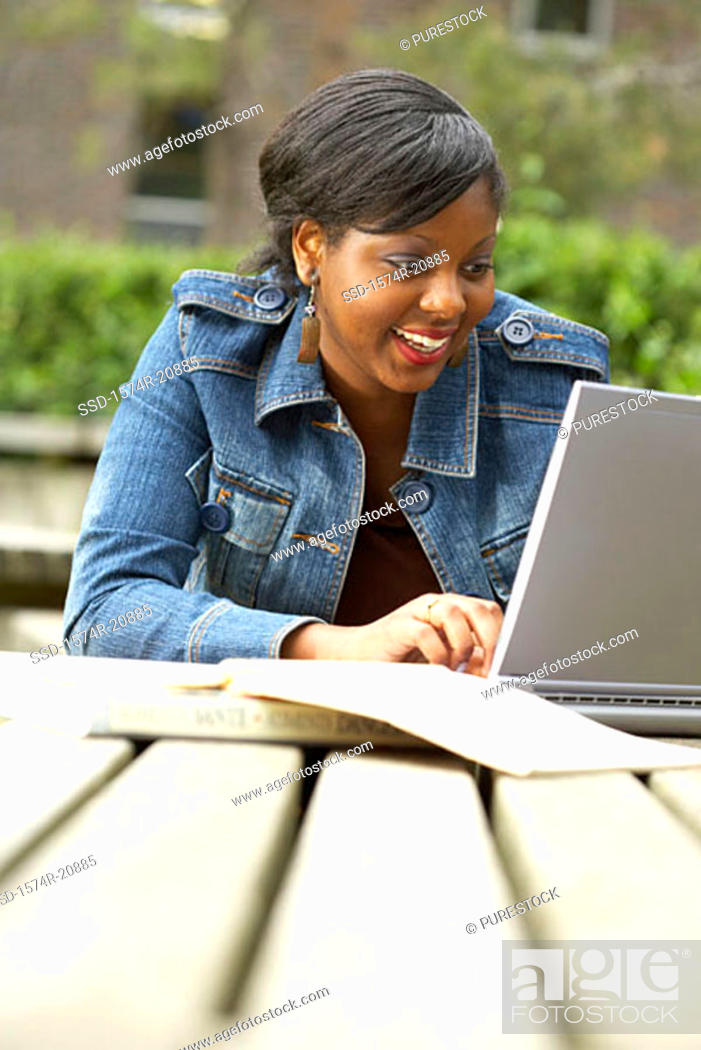 Stock Photo: College student using a laptop and smiling.