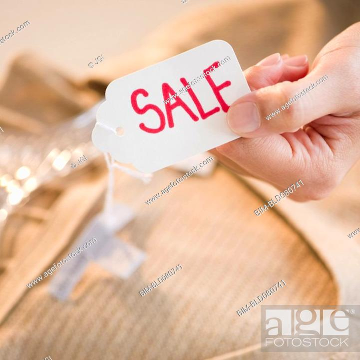 Stock Photo: Hand holding clothing sale tag.