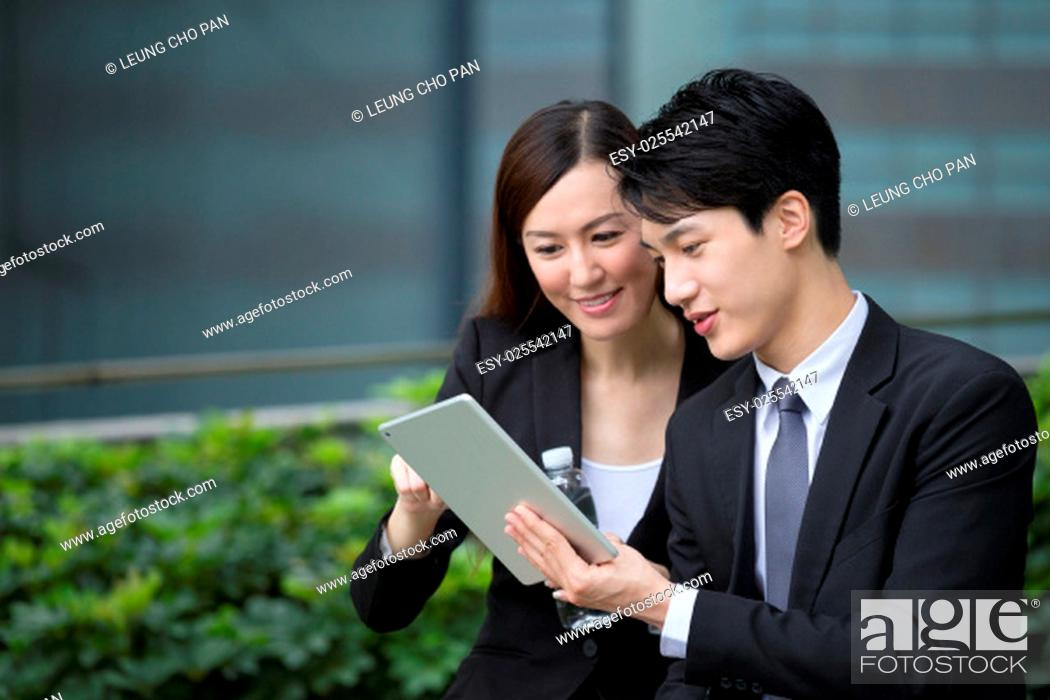Stock Photo: Business man and woman discuss about the financial plan on digital tablet.