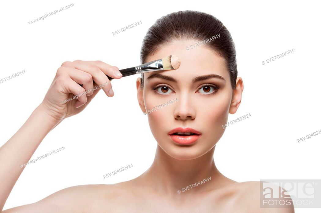 Stock Photo: Beautiful young woman applying liquid foundation with brush. Isolated over white background. Copy space.