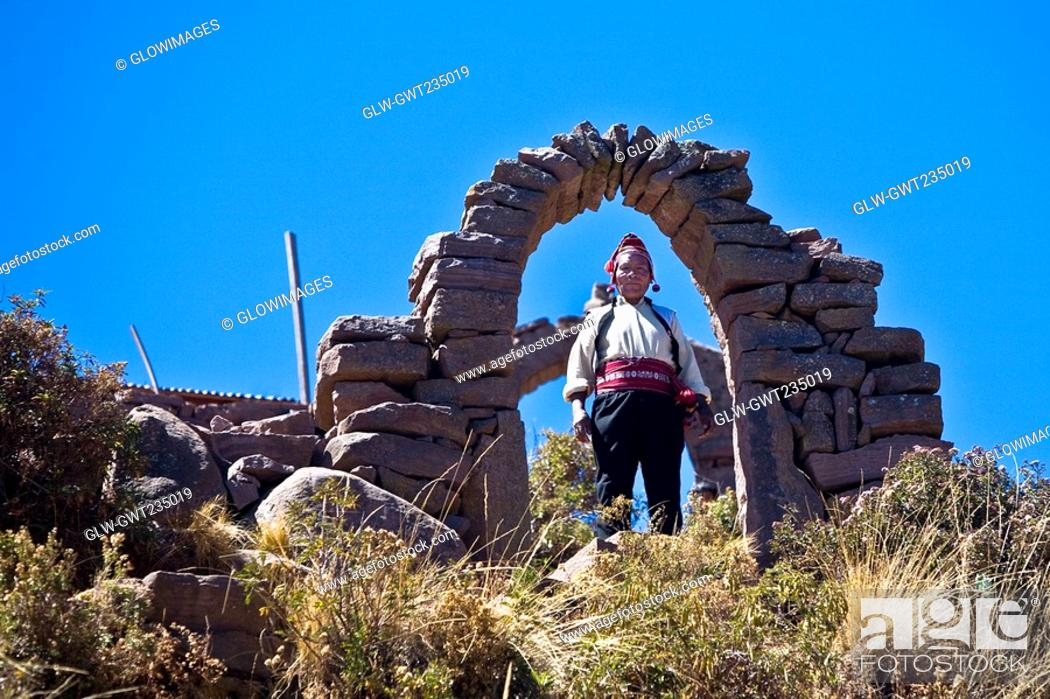 Stock Photo: Portrait of a young woman standing under a stone arch, Taquile Island, Lake Titicaca, Puno, Peru.