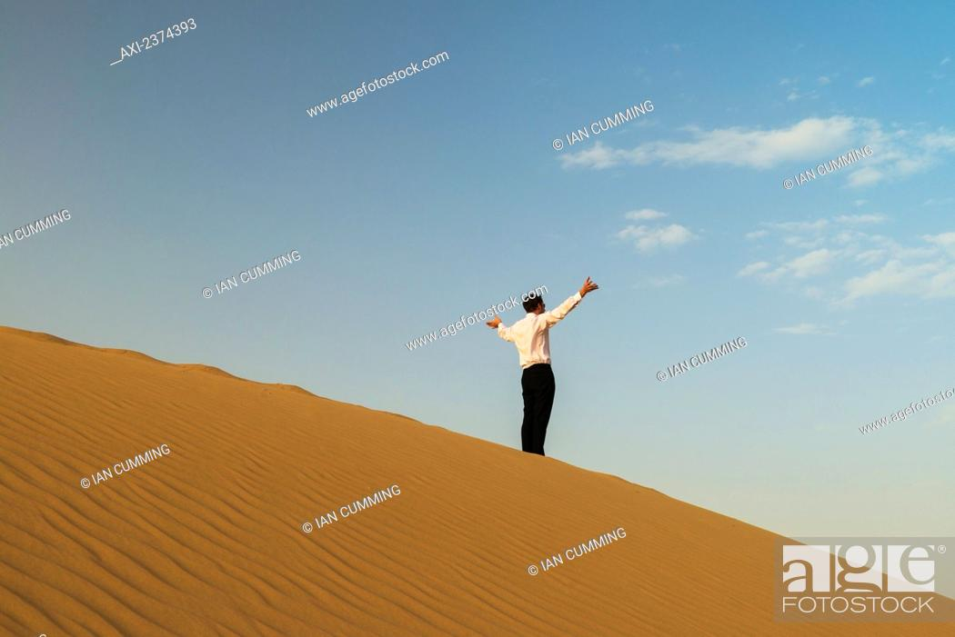 Man in smart clothes waving for attention on top of sand