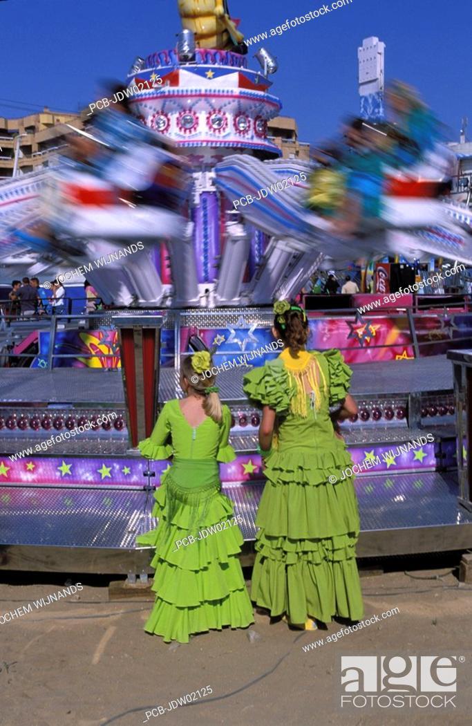 Stock Photo: Sanlucar de Barrameda, two women in flamenco dress watching a fun fair attraction.