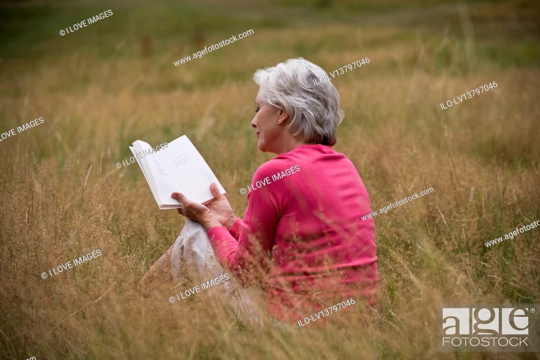 Stock Photo: A senior woman sitting on the grass, reading a book, rear view.