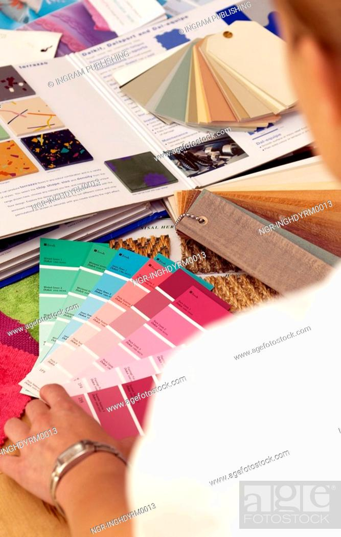 Stock Photo: Close-up of a woman looking at shade cards of paints on a table.