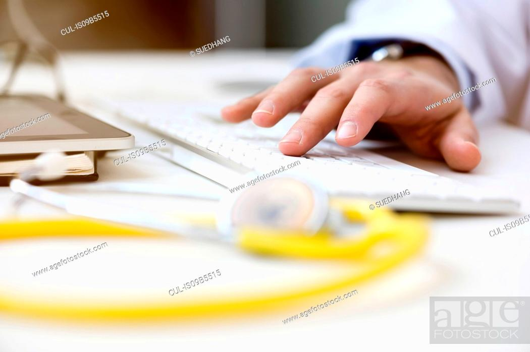 Stock Photo: Doctor using computer, tying on keyboard, close-up.