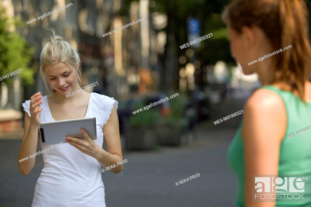 Stock Photo: Germany, North Rhine Westphalia, Cologne, Young women with digital tablet on street, smiling.