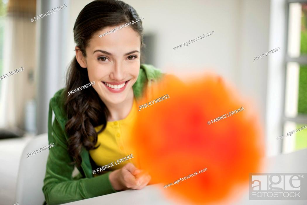 Stock Photo: Happy woman holding a feather duster.