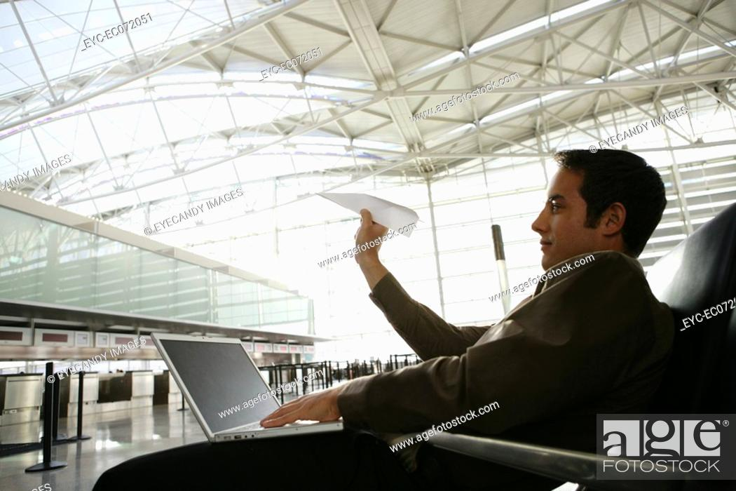 Stock Photo: Young businessman throwing paper airplane in airport.