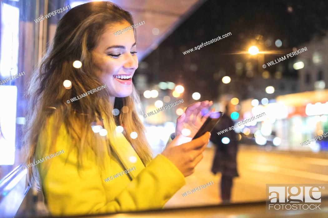Stock Photo: Happy woman waiting for the bus in the city at night, London, Great Britain.
