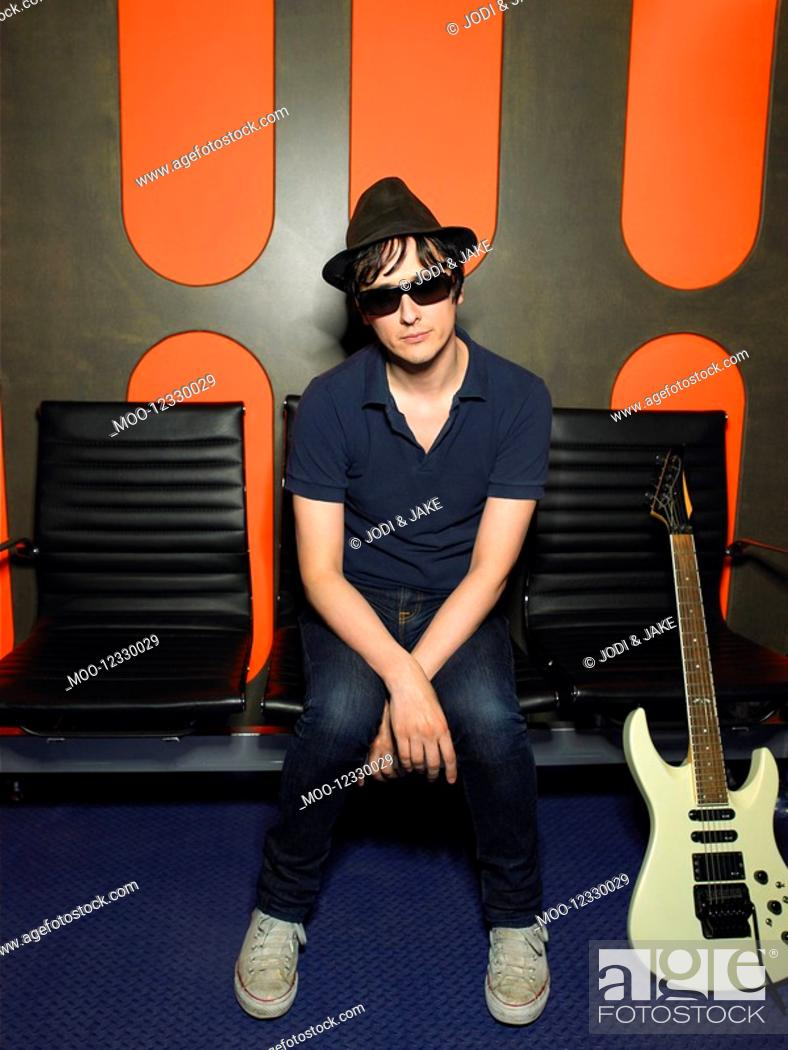 Stock Photo: Young man in sunglasses with guitar portrait.