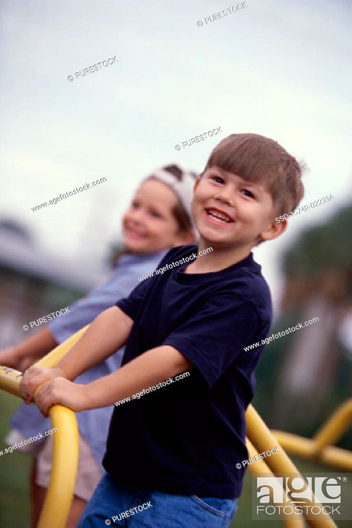 Stock Photo: Portrait of two boys standing on a merry-go-round.