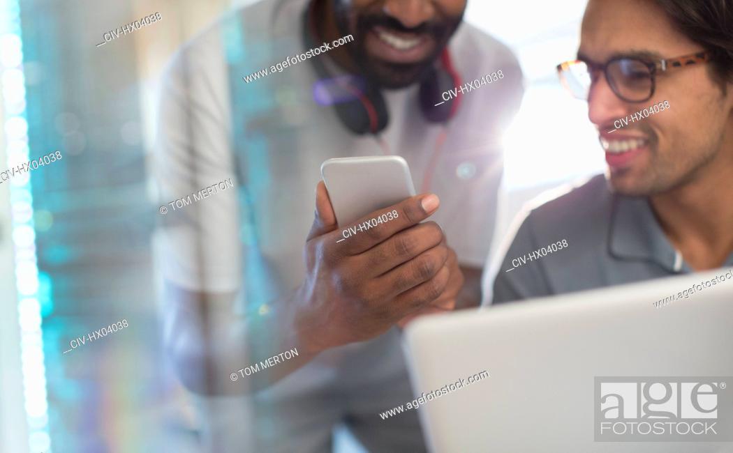 Stock Photo: Smiling creative businessmen using smart phone.