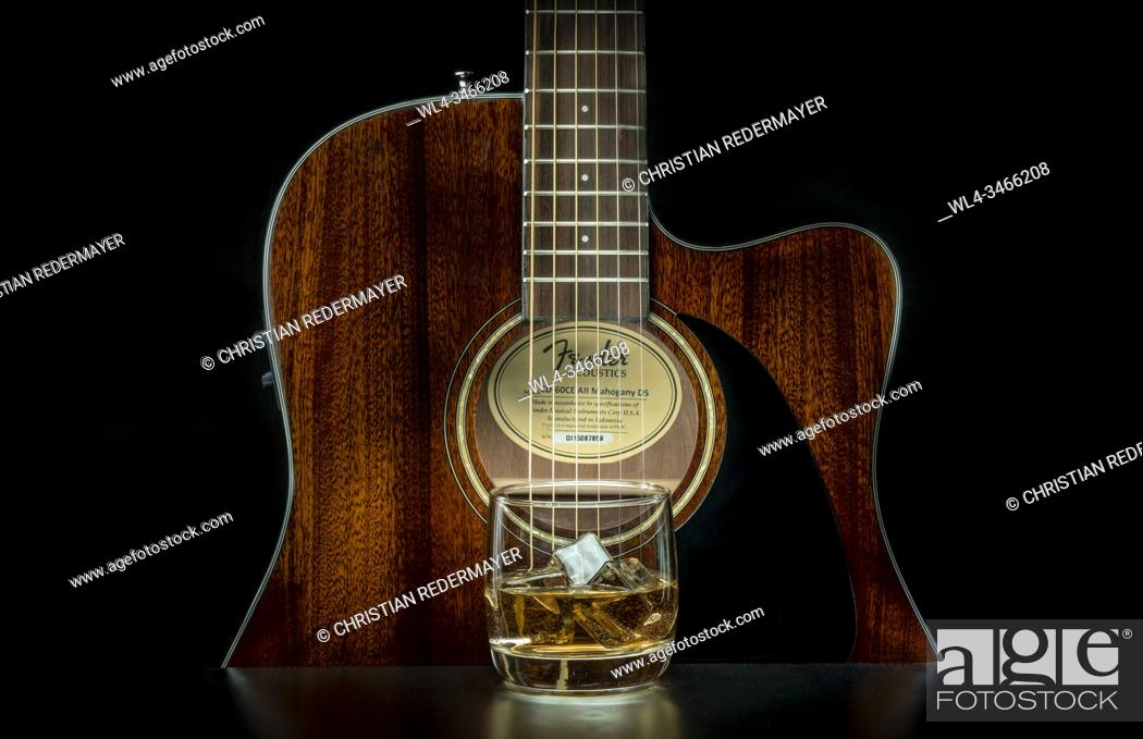 Stock Photo: Music concept image, classic guitar with a Whiskey glas on a black background, Jazz, rock, blues music or life style concept.