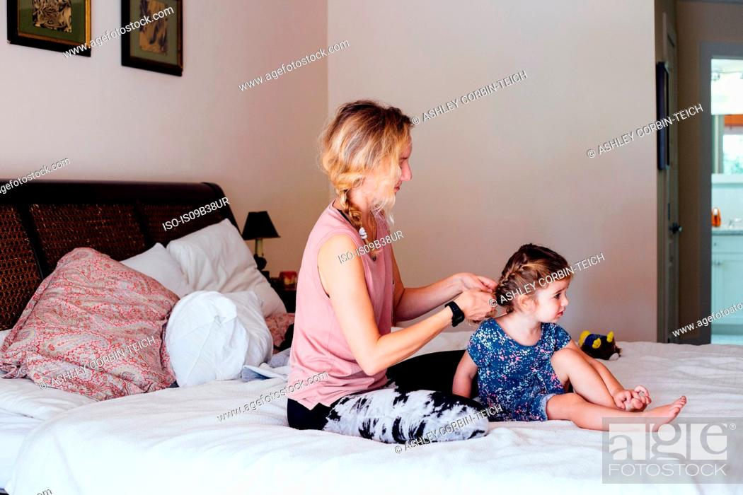 Stock Photo: Woman sitting on bed plaiting toddler daughter's hair.