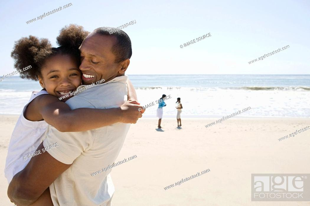 Stock Photo: Father and daughter hugging on a beach.
