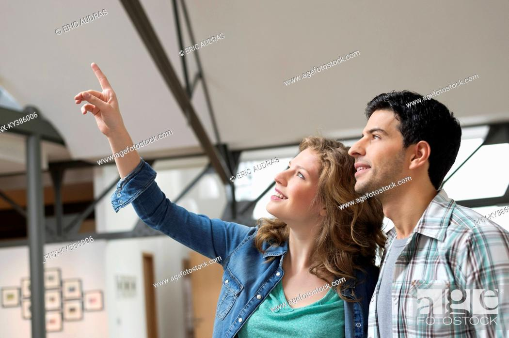Stock Photo: Happy woman pointing with her husband beside her.