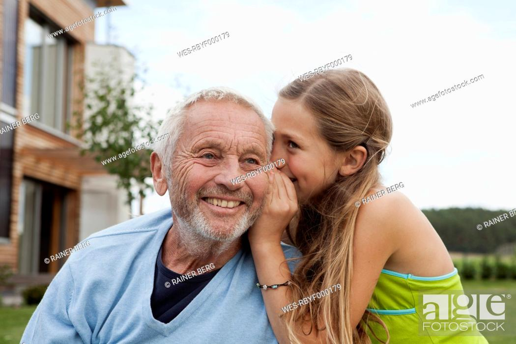 Stock Photo: Germany, Bavaria, Nuremberg, Granddaughter whispering in grandfathers ear.