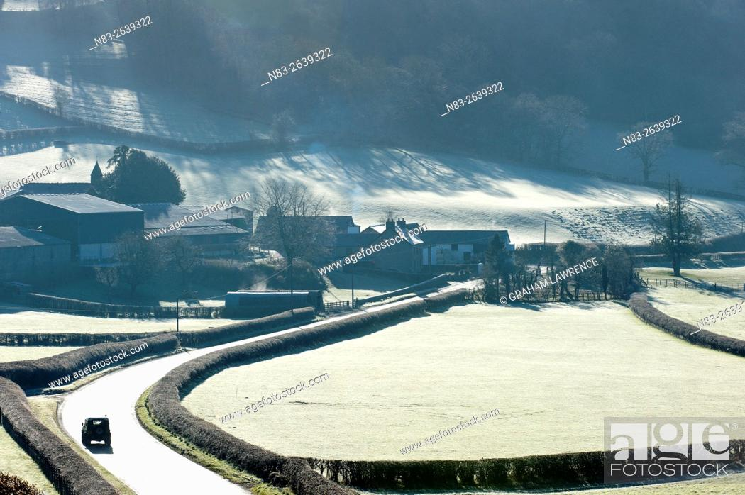 Stock Photo: A motorist drives through a frosty landscape along the road between Aberedw and Builth Wells, Powys, UK.