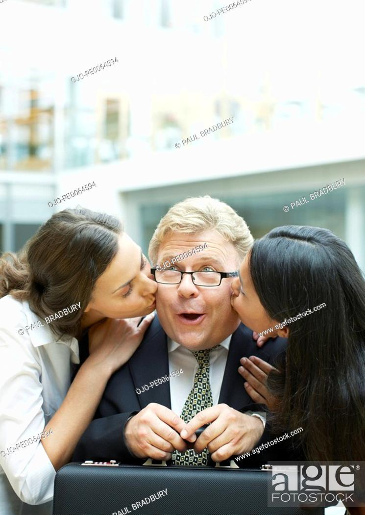 Stock Photo: Women kissing surprised businessman.