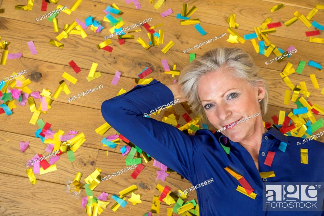 Stock Photo: Portrait of smiling senior woman lying on floor covered with confetti.