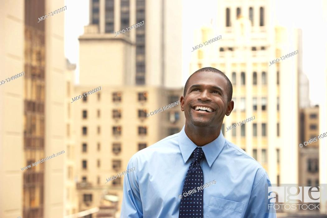 Stock Photo: Business man looking up standing in city half length.