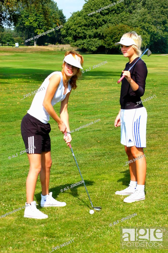 Stock Photo: Two girls, golfer, play golf on a golf course in Ystad, Scania, Sweden.
