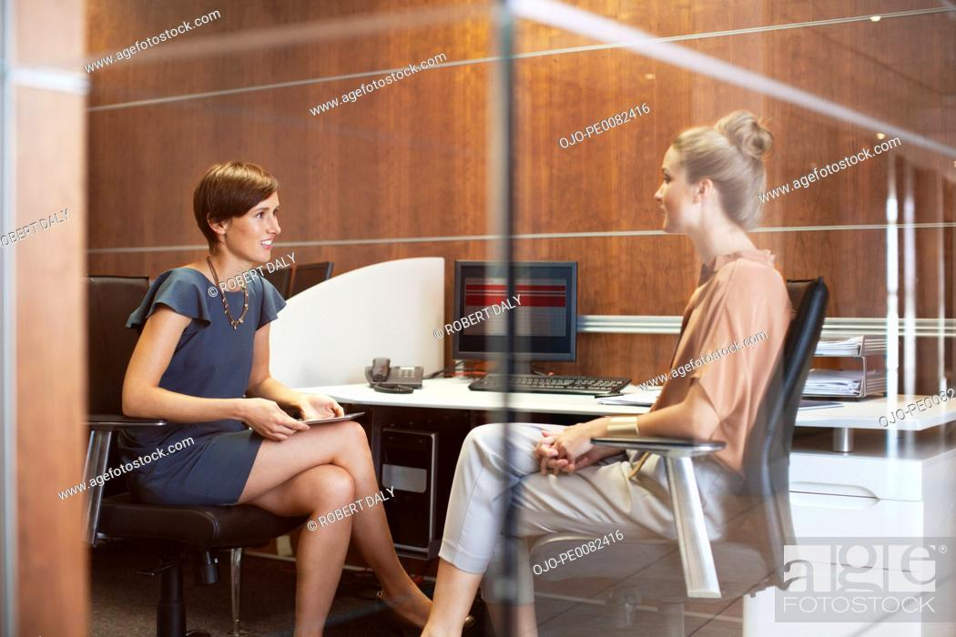 Stock Photo: Businesswomen talking in office.