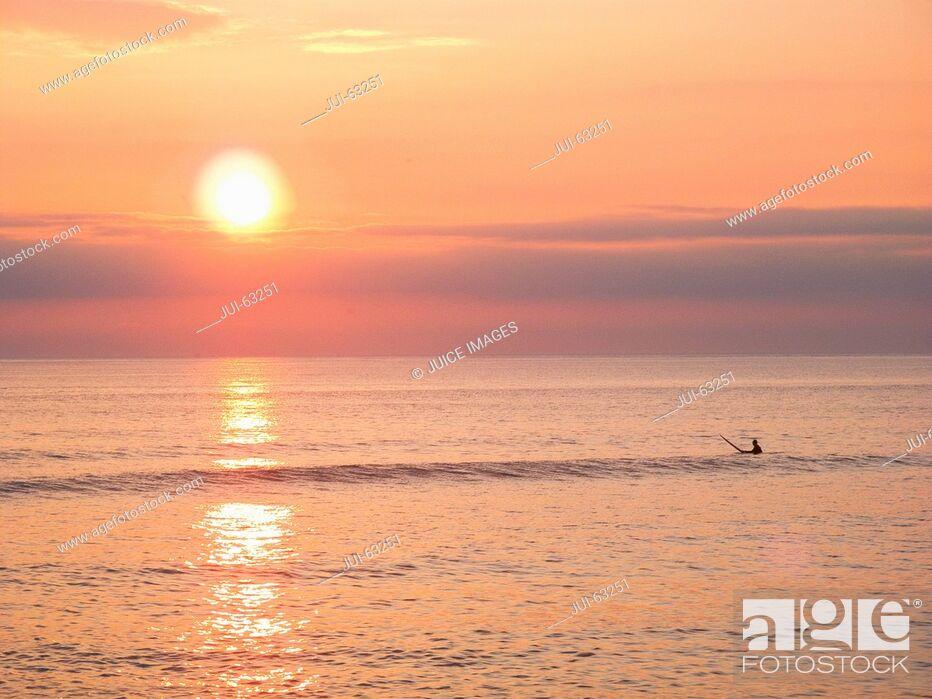 Stock Photo: Surfer on surfboard at Sunset.