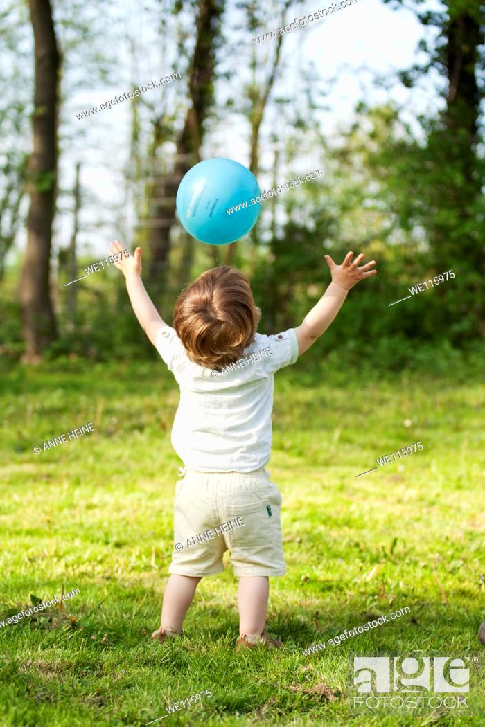 Stock Photo: child throwing ball in midair, arms stretched out and up, from back.