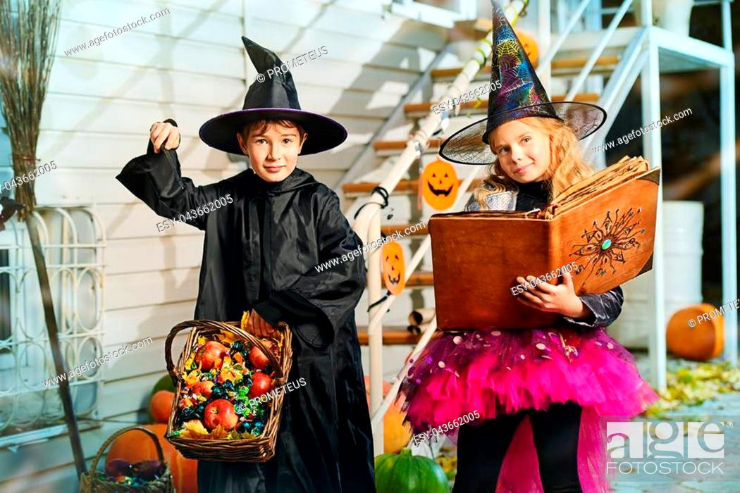 Imagen: Happy children in a costumes of witches and wizards celebrating halloween. Trick or treat. Halloween party.