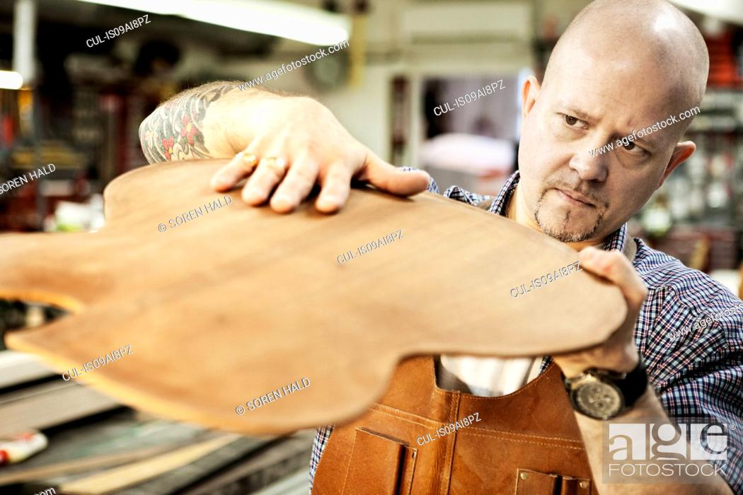 Imagen: Guitar maker checking wooden guitar shape in workshop.