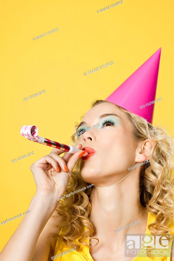 Stock Photo: Young woman wearing party hat with party blower.