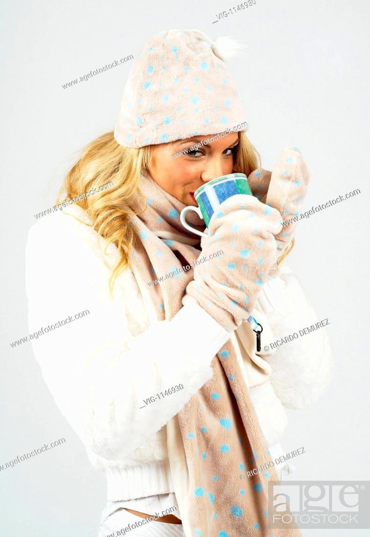 Stock Photo: AUSTRIA , VIENNA , 11.02.2008, Young woman wearing a woolen ski hat, gloves and scarf, drinking from a mug - Vienna, Vienna, AUSTRIA, 11/02/2008.