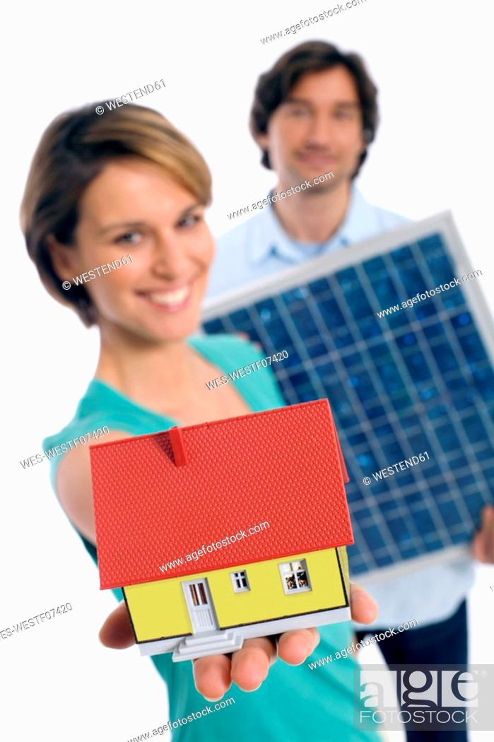 Stock Photo: Couple holding solar panel and house.