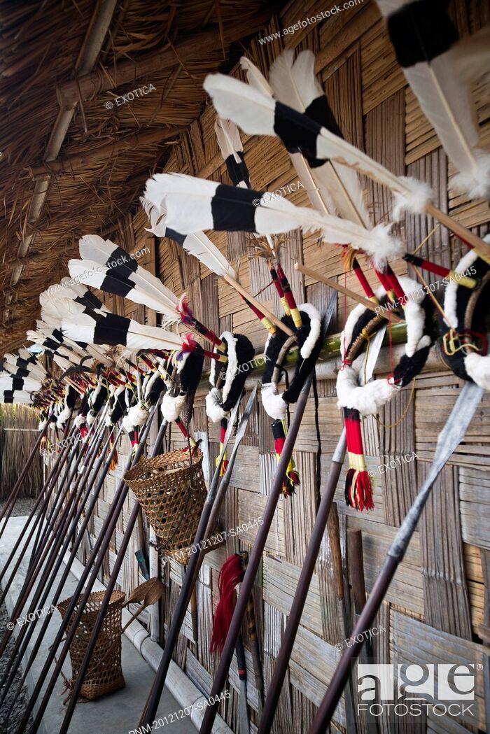 Stock Photo: Traditional Naga tribal weapons and headdresses on wall during the annual Hornbill Festival at Kisama, Kohima, Nagaland, India.