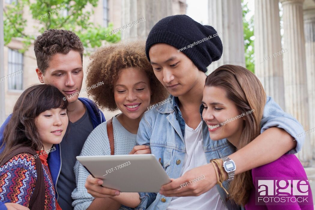 Stock Photo: Young man showing digital tablet to multi-ethnic friends.