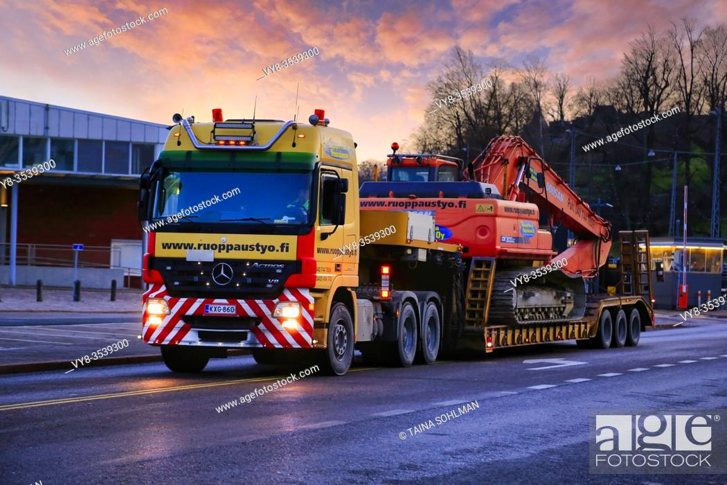 Stock Photo: Mercedes-Benz Actros truck low loader trailer Ruoppaustyo transports Doosan DX 300 LC excavator at sunset time. Helsinki, Finland. December 19, 2019.