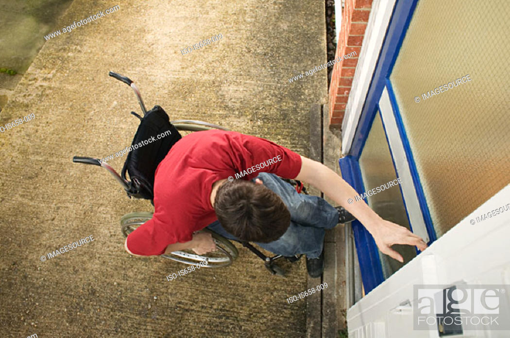 Stock Photo: Disabled man opening front door.