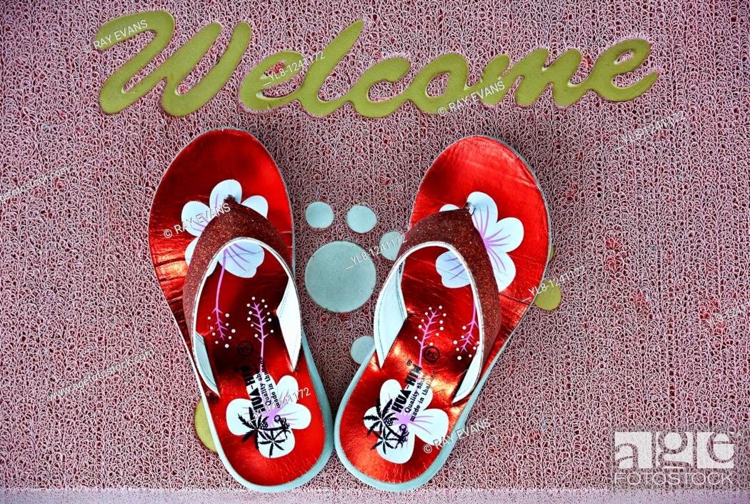 Stock Photo: Brightly colored flip flops on a home welcome door mat.