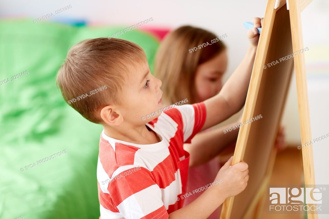 Stock Photo: happy kids drawing on chalk board at home.