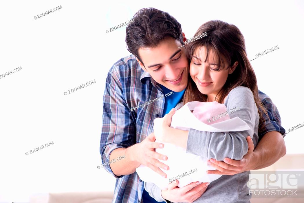 Imagen: Young parents with their newborn baby near bed cot.