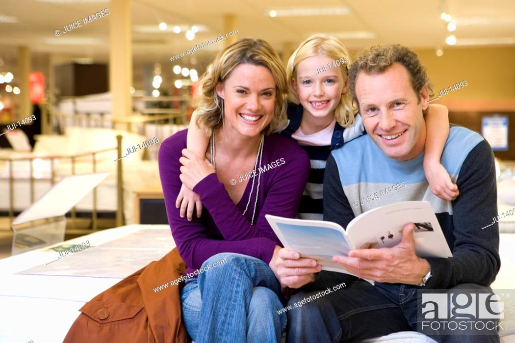 Stock Photo: Young couple in furniture shop, daughter 6-8 embracing parents with brochure, smiling, portrait.