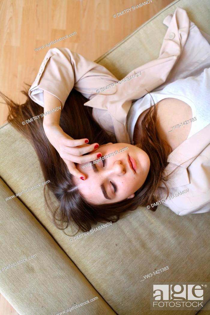 Stock Photo: Portrait of a young blond woman lying on sofa.