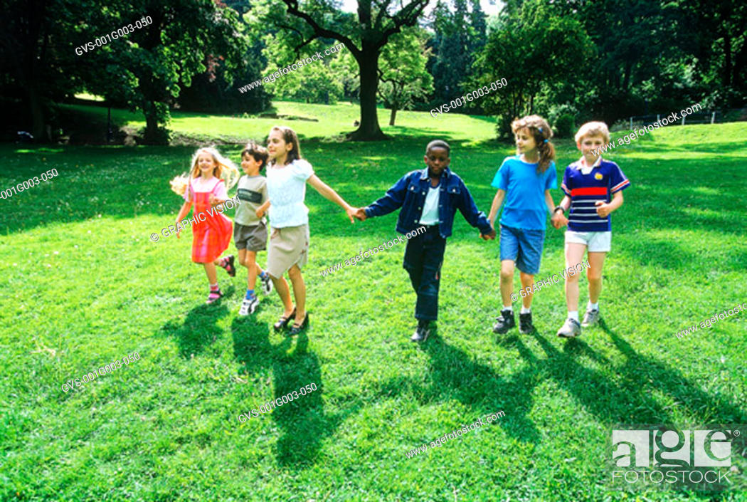Stock Photo: Young children holding hand walking on a lawn.
