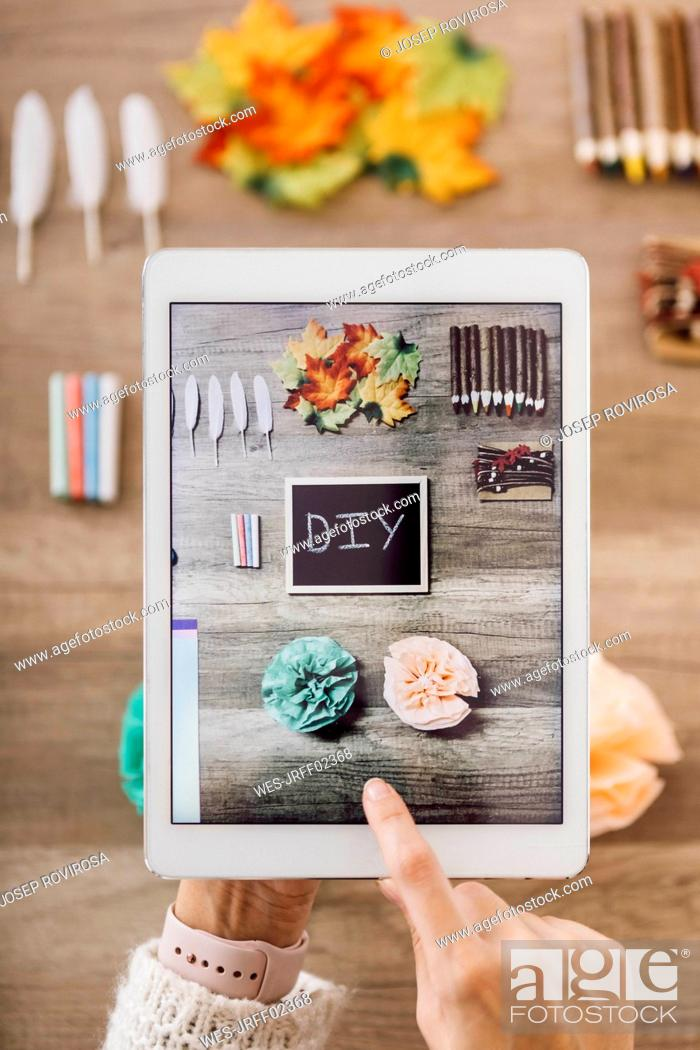 Stock Photo: Top view of young woman making photos with the tablet for her blog of handmade paper flowers.