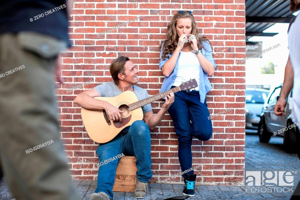 Imagen: Two street musicians playing together, entertaining pedestrians.